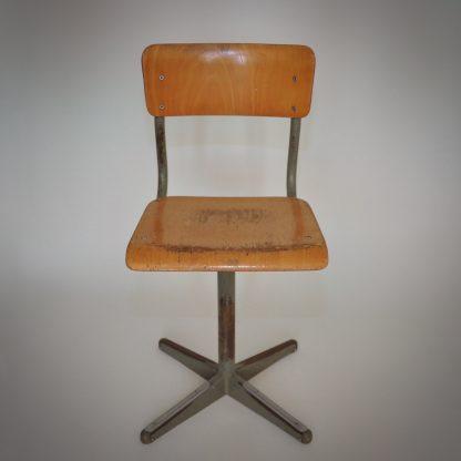 Vintage industriele schoolstoel met metalen staander en houten zitting en rugleiuning. In vintage geleefde conditie met mooie gebruikssporen