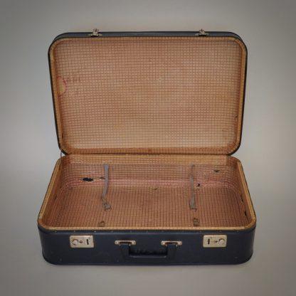 Vintage blauwe reiskoffer met vergeelde en geleefde binnenzijde.