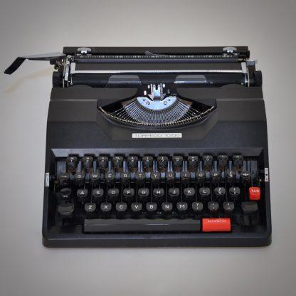 Zwarte vintage typemachine met beschermkap en draagbaar. In uitstekende conditie met semi-automatische functies. Echt een voorloper van de automatische typemachine. Geproduceerd in de jaren 80. Leuke rode knoppen en strakke zwarte uitvoering.
