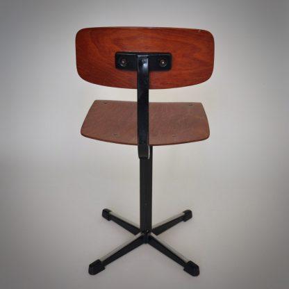 Vintage schoolstoel van fabrikant Marko uit Nederland. Plywood donkerbruine zitting en rugleuning. Zwart metaal staander met kruispoot.