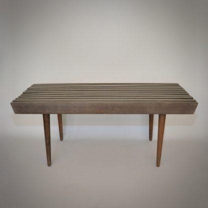 rechthoekig bijzettafeltje met groen blad bestaande uit spijlen van hout en taps toe lopende pootjes in houtkleur.
